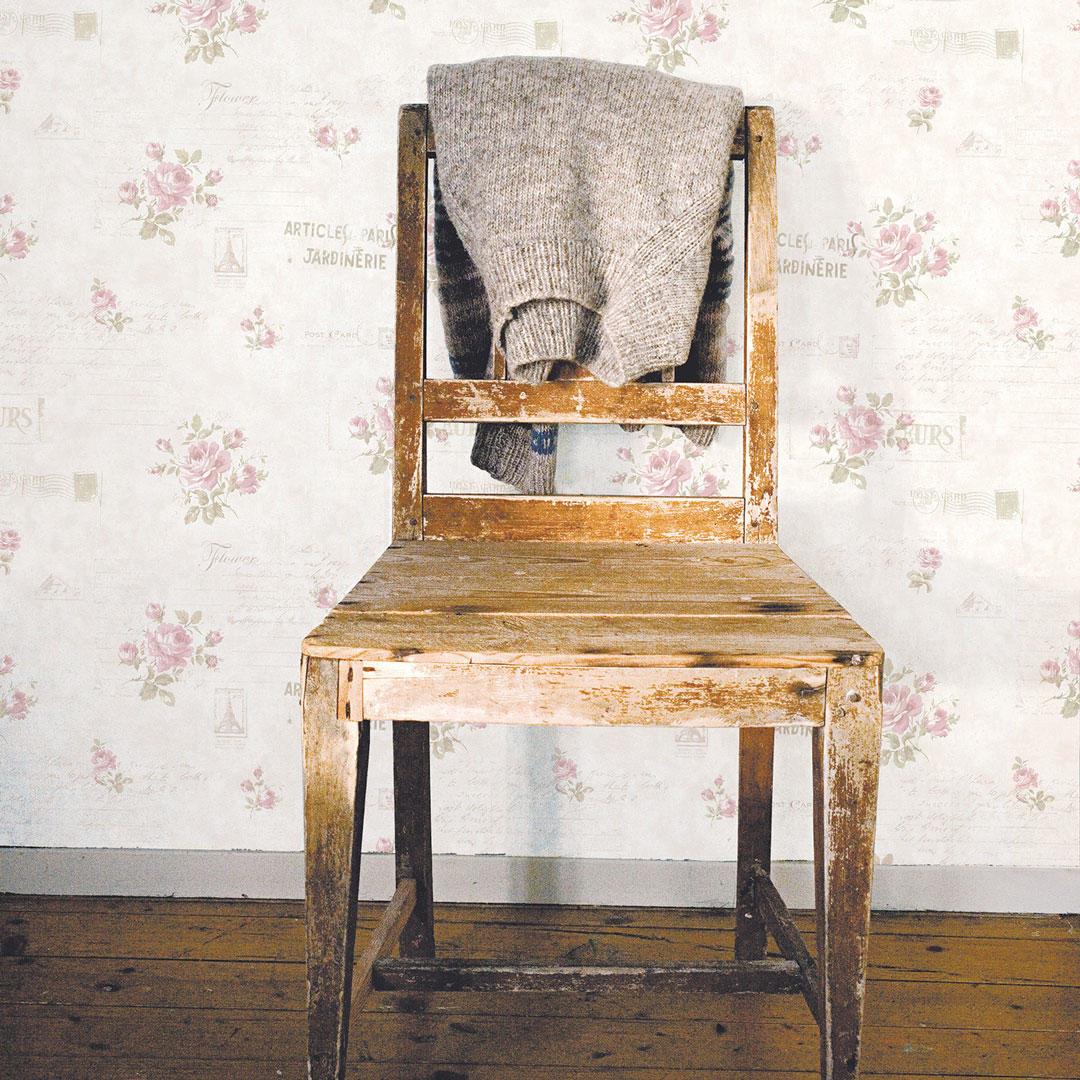 Vintage roses tapet på vegg bak en slitt stol