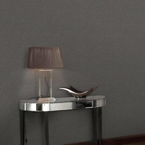 Grå vegg med tapet og lite bord med lampe foran