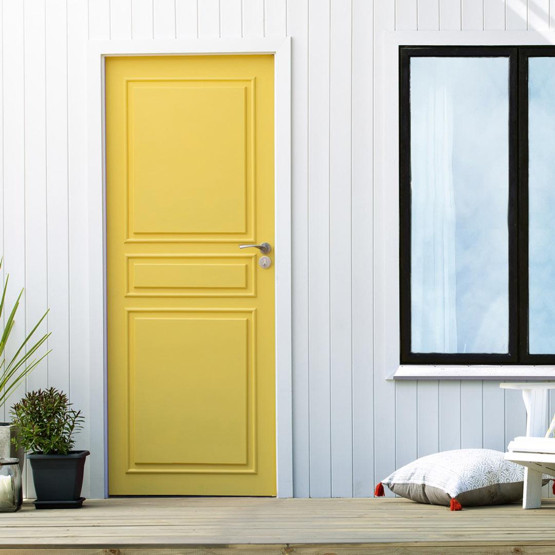 Inngangspartiet til et hus med gul nymalt ytterdør