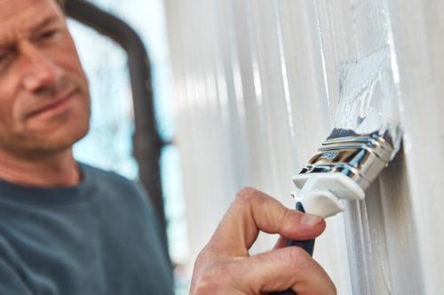 Nærbilde av en mann som maler fasaden hvit